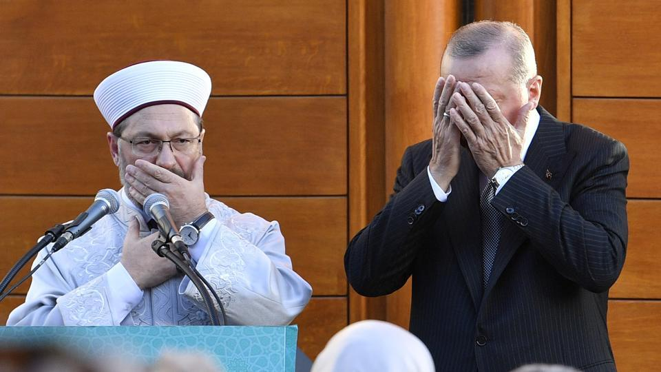 Turkish President Recep Tayyip Erdogan (R) and Diyanet President Ali Eras cover their faces during a prayer on occasion of the opening of the new mosque in Cologne, Germany. (Martin Meissner / AP)