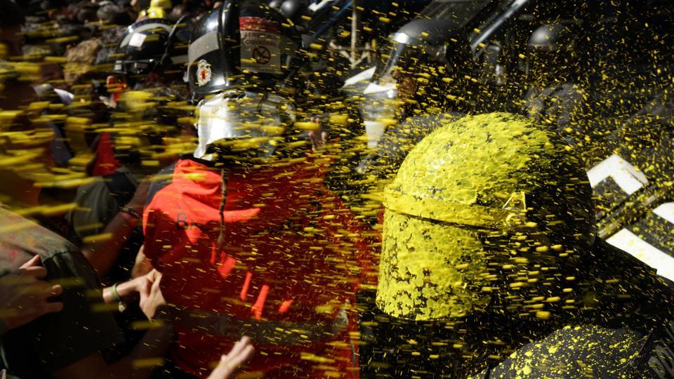 Pro independence demonstrators throw paint at Catalan police officers during clashes in Barcelona, Spain. (Daniel Cole / AP)