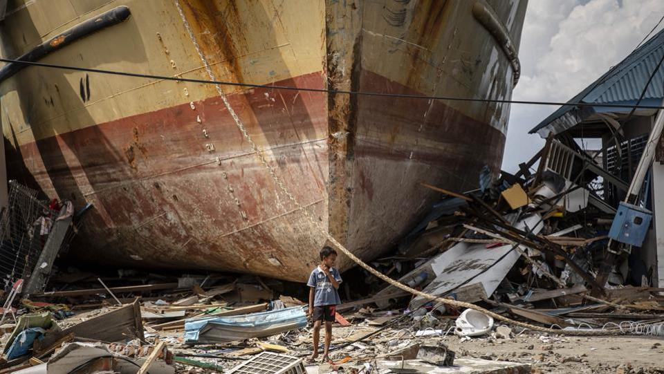 A boy stands in front of a stranded ship after a deadly tsunami struck the area in Donggala, Central Sulawesi, Indonesia. (Ulet Ifansasti / Getty Images)