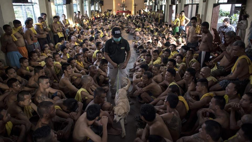 Inmates sit on the floor of Saint Dimas chapel as Philippine Drug Enforcement Agency personnel with a K9 dog look for contraband among inmates at the Manila City Jail. (Noel Celis / AFP)