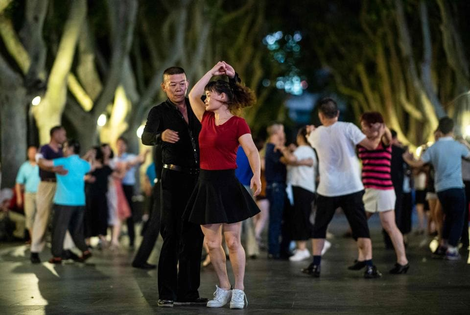 "A couple dances in a Shanghai park. But toes are tapping to an ever-quickening beat as ""square dancing"" -- as it is known in China -- booms. Teams are competing in dance-offs featuring thousands of contestants, while a thriving market of dance-related paraphernalia and mobile apps catches the attention of the business world. (Johannes Eisele / AFP)"