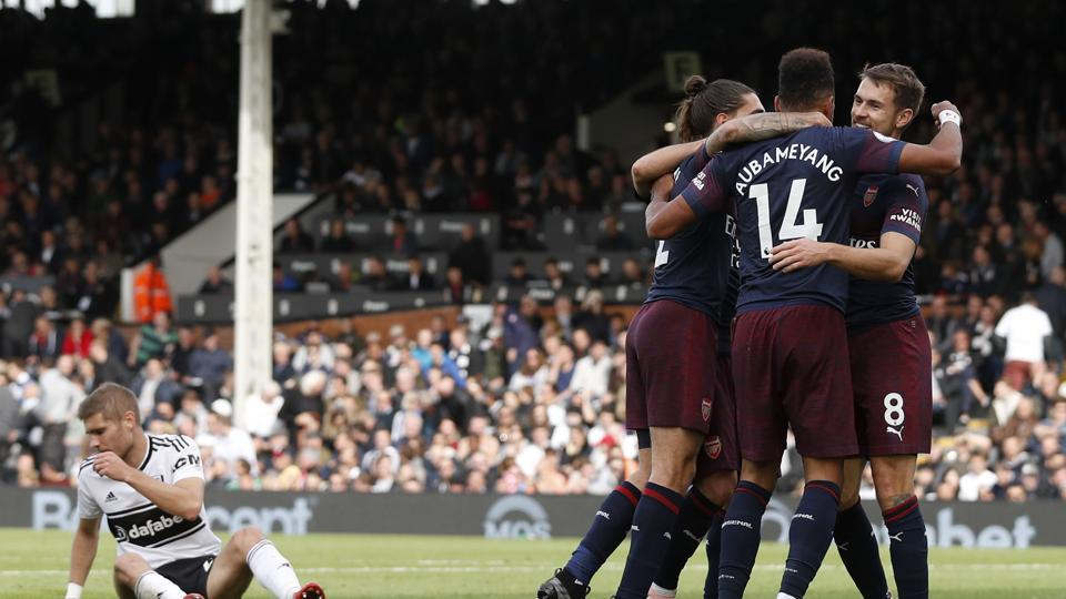 Arsenal's Gabonese striker Pierre-Emerick Aubameyang celebrates with teammates after scoring the team's fifth goal during the English Premier League football match between Fulham and Arsenal at Craven Cottage.
