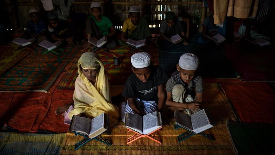 "Saleema Khanam (L), studies inside a makeshift madrassa with other students in Kutupalong camp, near Cox's Bazar. She takes her position in the front, flanked by two brothers, and opens the book. ""I come here to learn the Quran. My mother wants me and my brothers to learn, to become better people,"" the young student told AFP. (Chandan Khanna / AFP)"