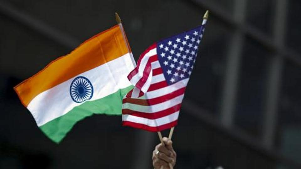 A man holds the flags of India and the US flag in New York.