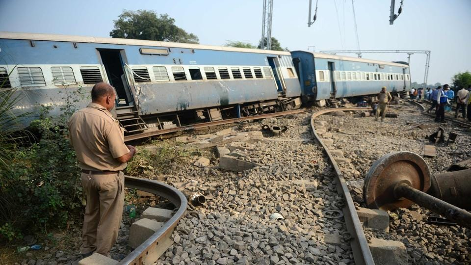 A police personnel stands the site where the engine of the New Farakka Express train derailed along with eight coaches near Harchandpur Railway station in Rae Bareli on October 10.