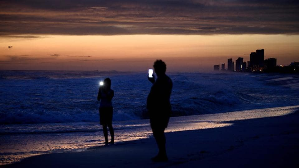 People visit the beach while waiting for Hurricane Michael in Panama City Beach, Florida. (Brendan Smialowski / AFP)