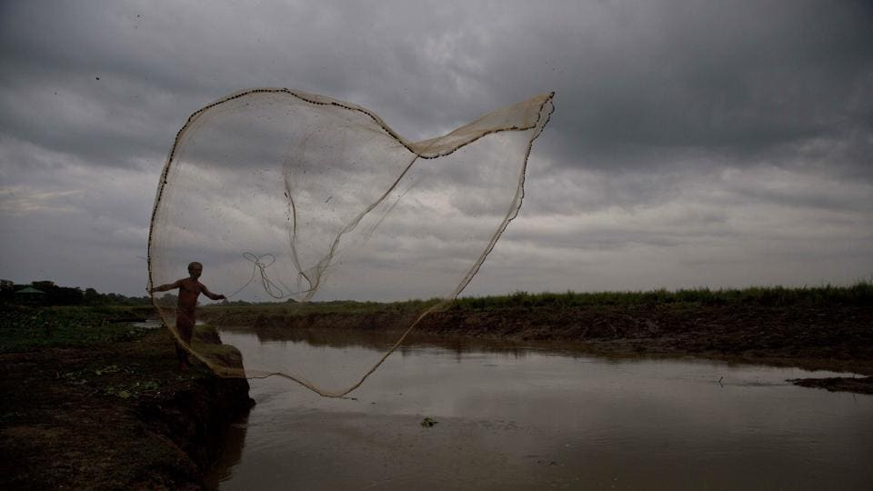 A fisherman casts his fishing net out for fish in Kaziranga, Assam. (Anupam Nath / AP)