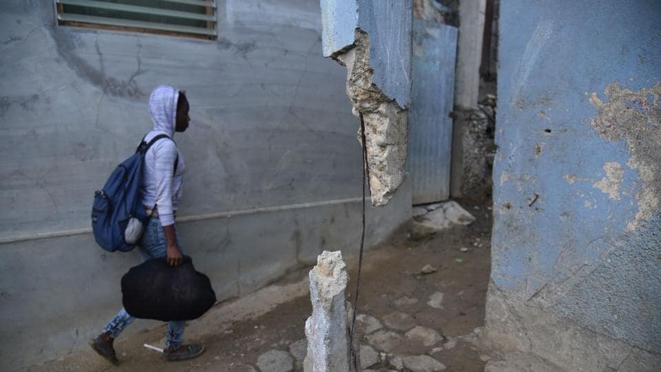 A girl walks next to a house that suffered some damage after an earthquake hit the city of Port-de-Paix, Haiti. (Hector Retamal / AFP)