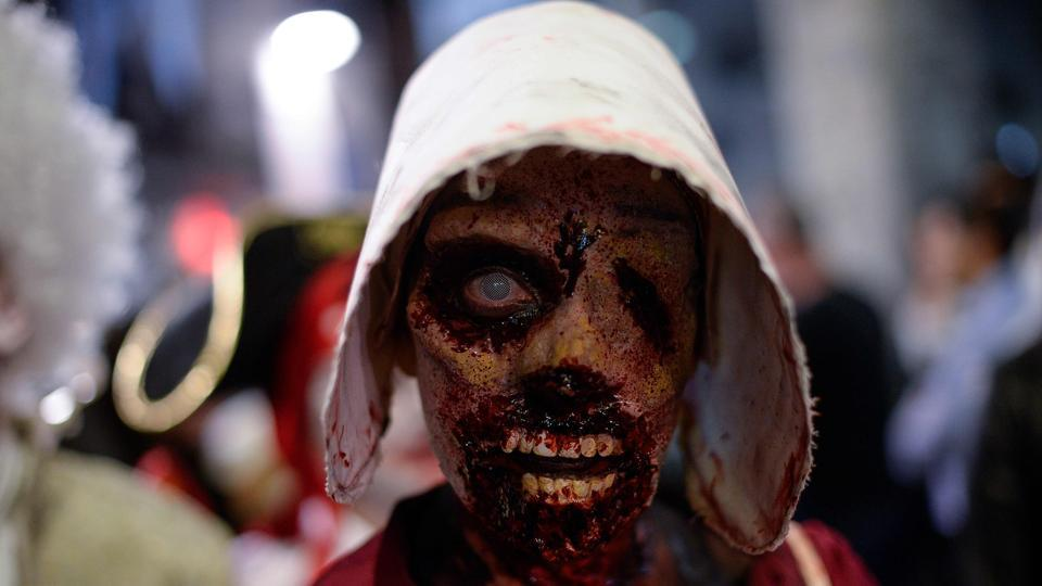 "A woman sporting zombie make-up and dressed up as characters of the US TV series ""The Handmaid's Tale"" takes part in the Zombie Walk event in the Catalan city of Sitges, within the framework of the 51st edition of the SITGES – International Fantastic Film Festival of Catalonia. (Josep Lago / AFP)"
