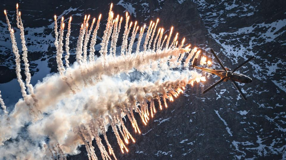 A Super Puma Cougar helicopter releases flares over Brienz in the Bernese Alps, during the annual live fire event of the Swiss Air Force at the Axalp. (Fabrice Coffrini / AFP)