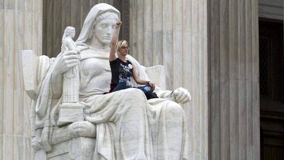 Demonstrator Jessica Campbell-Swanson of Denver, Colorado, sits on the lap of the 'Contemplation of Justice' statue as protestors take the steps of the US Supreme Court against the appointment of Supreme Court nominee Brett Kavanaugh in Washington DC. (Jose Luis Magana / AFP)