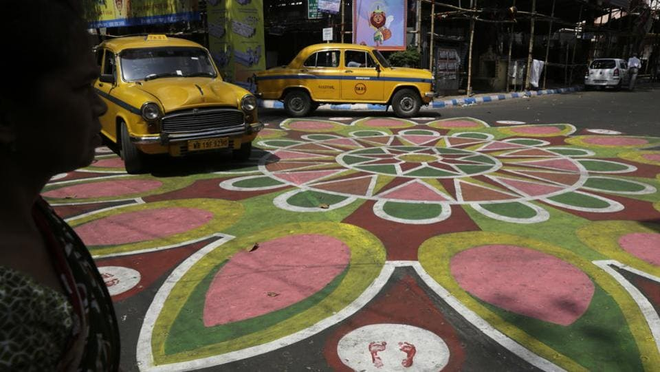 A woman, and two yellow cabs prepare to cross an intersection painted with colours ahead of the Hindu festival of Durga Puja in Kolkata, West Bengal. (Bikas Das / AP)