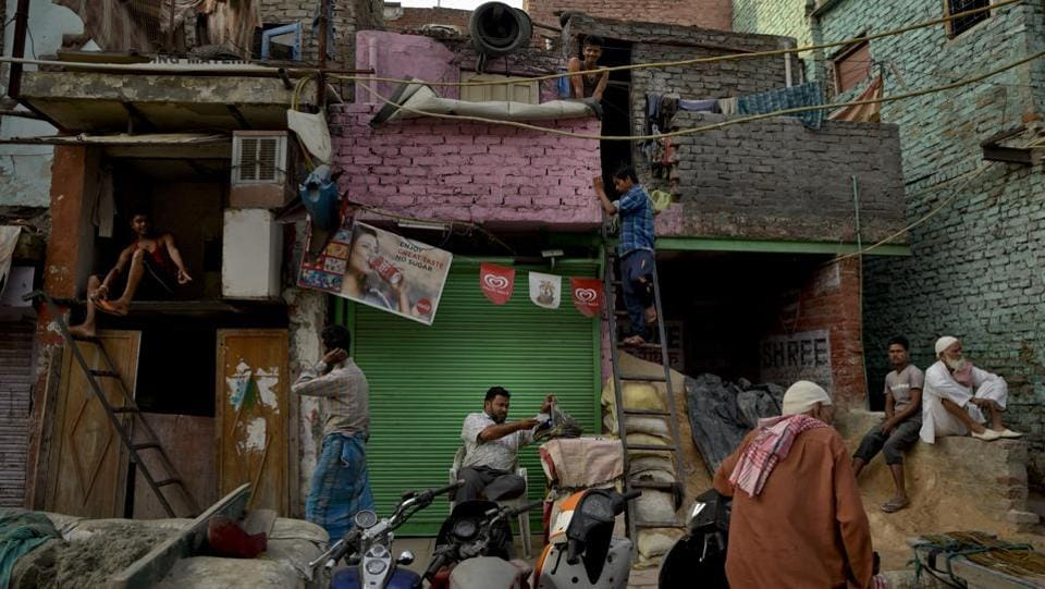 Migrant workers from eastern India prepare themselves for the day outside their cramped accommodation in the old quarters of Delhi. (R S Iyer / AP)