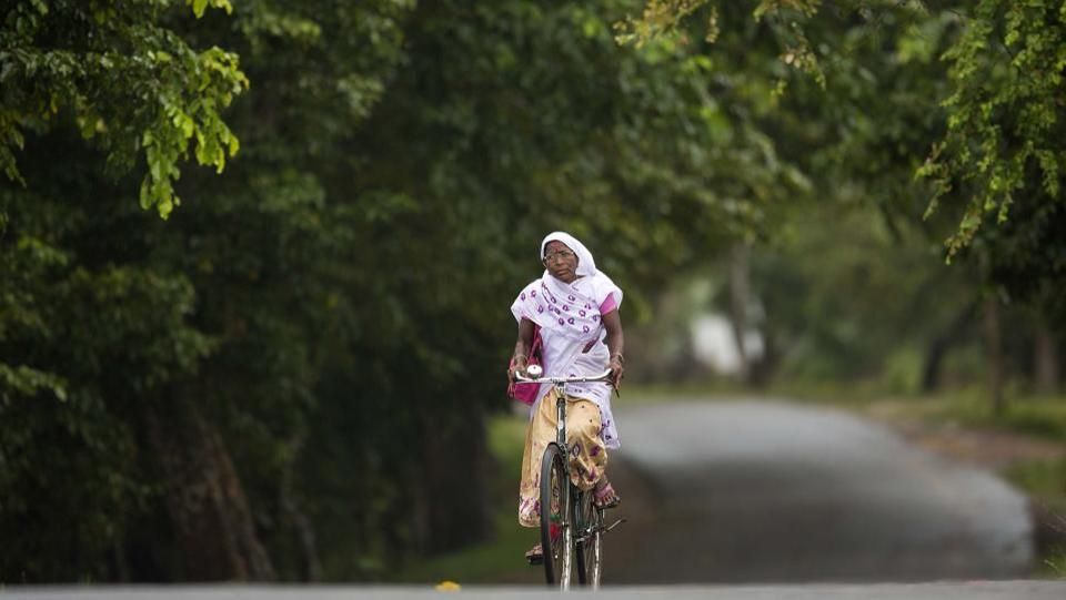 An Assamese woman in traditional attire rides a bicycle in Kaziranga, Assam. The area is famous for the Kaziranga National Park which has the world's largest concentration of Indian one-horned rhinoceros. (Anupam Nath / AP)
