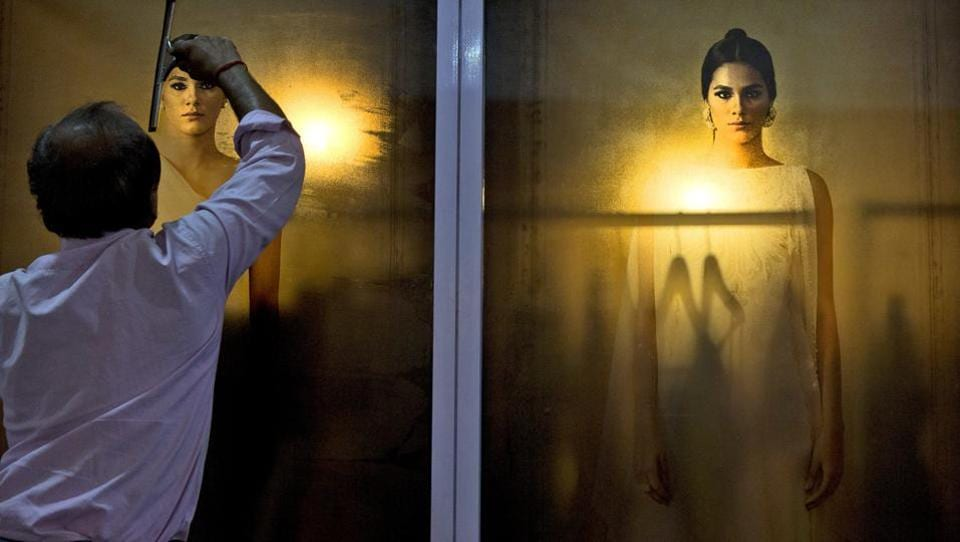 A worker pastes a photograph of a model at the exhibition centre of various designers at the start of the Lotus Makeup India Fashion Week in New Delhi, India. (Manish Swarup / AP)