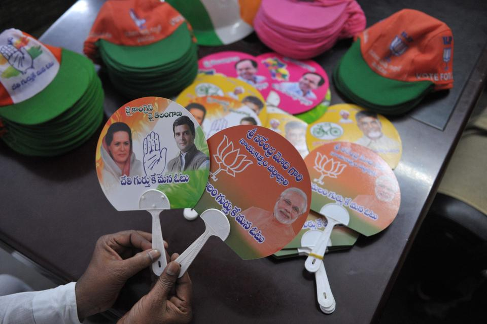 Indian holds election campaign fans theg Bharatiya Janata Party (BJP) (R) and Indian National Congress party (L) ahead of the upcoming Telangana state legislative assembly elections in Hyderabad on October 4, 2018. - The Southern Indian state elections are due to be held in November or December 2018 to constitute the second Legislative Assembly. (Photo by NOAH SEELAM / AFP)