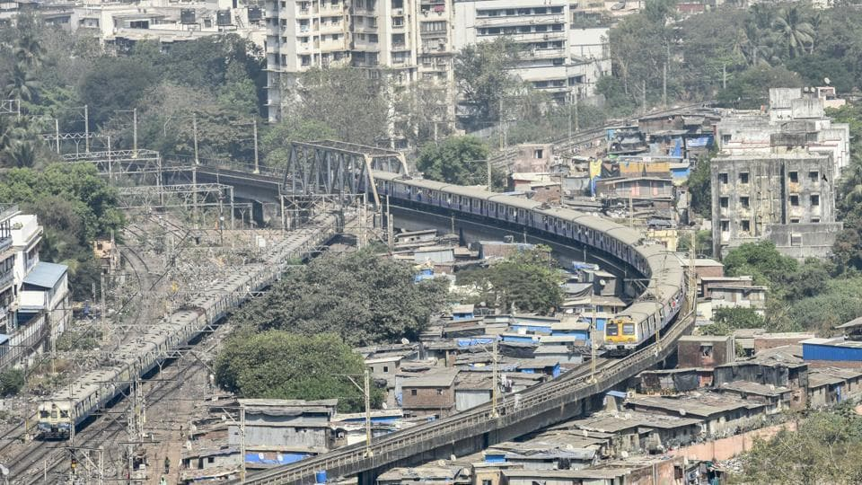 A local train moves on an elevated track over a slum area at Wadala, Mumbai, February 1, 2018