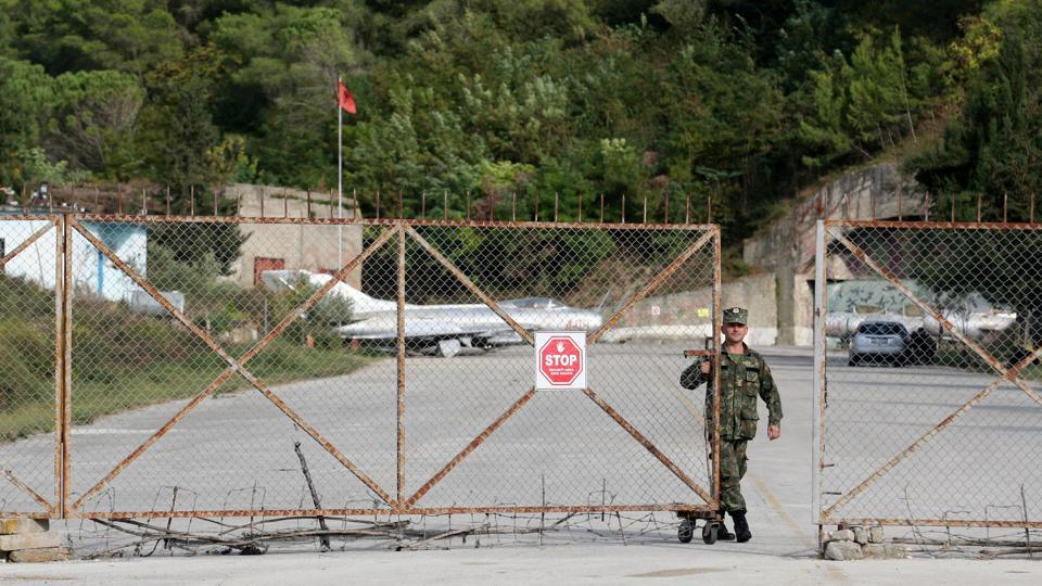 An Albanian Armed Forces member closes the gate to Kucova Air Base. The runway, conceived by Soviet planners who stored dynamite under the airfield to blow it up should it fall into enemy hands and built by political prisoners in the 1950s, has good weather conditions all year round. (Florion Goga / REUTERS)