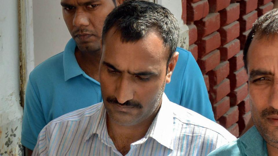 Police take Mahipal Singh, who is accused of shooting a judge's wife and son, to a court, in Gurugram, Sunday, Oct 14, 2018.