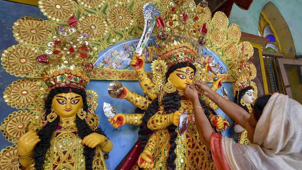 An idol of Goddess Durga being decorated with gold ornaments at a traditional 189 years old puja house on Mahashasthi, indicating the beginning of the Durga Puja festival, in Kolkata. (Ashok Bhaumik / PTI)