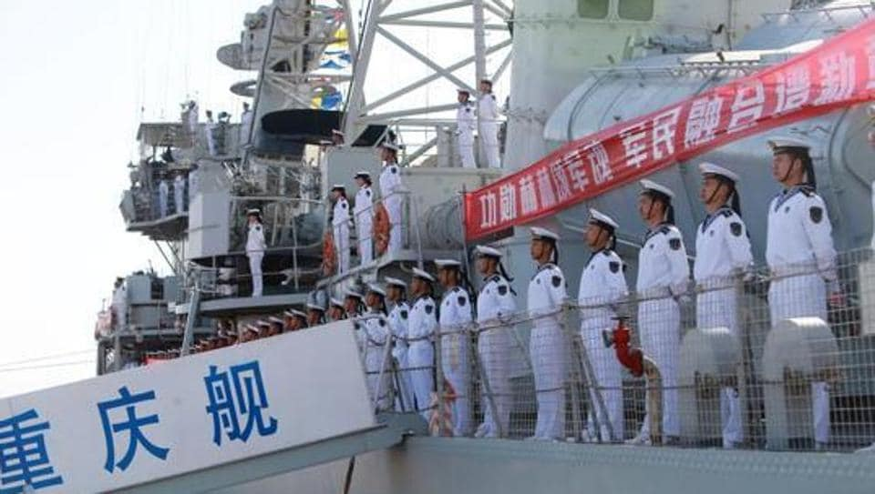 Chinese People's Liberation Army (PLA) navy soldiers stand on a decommissioned destroyer in an aircraft carrier theme park during a celebration event on China's Navy Day at Binhai New Area, Tianjin, China, in April 2017.