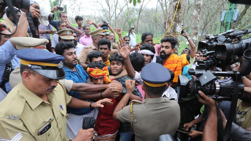 Police personnel tackling devotees protesting against the entry of women of all ages to the Sabarimala temple, at Nilakkal base camp in Pathanam, Kerala, on Tuesday.(Vivek Nair/HT Photo)