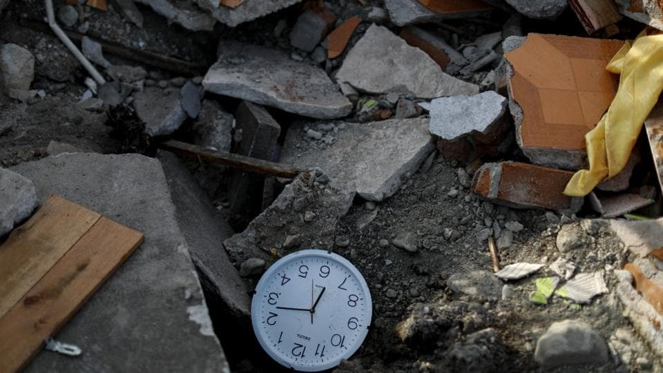 "A stopped clock shows the time a few minutes after the earthquake, lying among rubble. Some however, remain inconsolable. ""I don't know what to do next. There's nothing left for me here,"" said Kaharuddin, the fruit vendor still looking for his daughter's body under the pink concrete rubble of their former home. (Jorge Silva / REUTERS)"