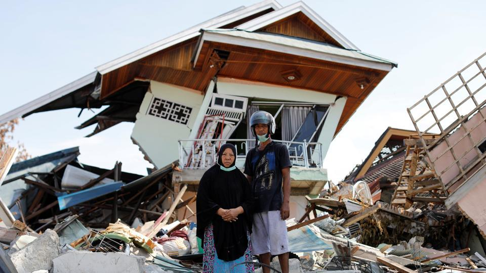 "Darmi, 48, and her brother Rusli, 43, outside her house. The destructive waves of soil smashed homes, cars and buildings into each other, carrying some hundreds of metres from their original position. ""It felt like the earth was alive,"" said Darmi, who saw half of her home collapse. ""It was opening up, swallowing people, and then closing again. And the noise was so loud. This loud cracking 'k-k-k-k' sound."" (Jorge Silva / REUTERS)"