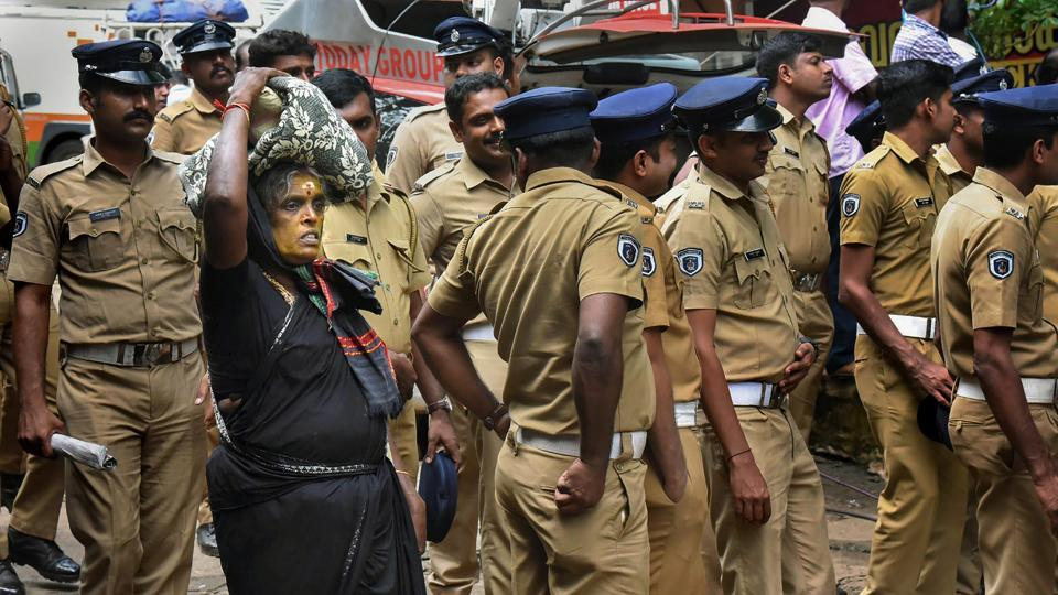 An elderly woman on her way to Sabarimala Temple as police personnel stand on guard, in Pathanamthitta on Wednesday. Sabarimala Temple is open to women of all age groups for the first time since Supreme Court announced its verdict.