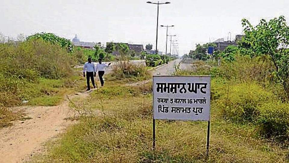 The 'shamshan ghat' signboard put up by villagers on an unfinished road at DLF Hyde Park in New Chandigarh.