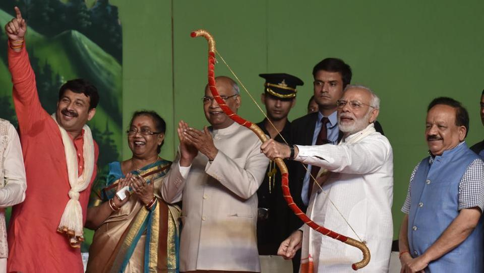 Prime Minister Narendra Modi (2R) holds a bow and arrow at an event as President Ram Nath Kovind and his wife Savita Kovind look on, ahead of the burning of an effigy of Ravana at an event marking the end of the festival of Dussehra at Luv-Kush Ramleela Committee in Lal Qila Maidan. (Sanjeev Verma / HT Photo)