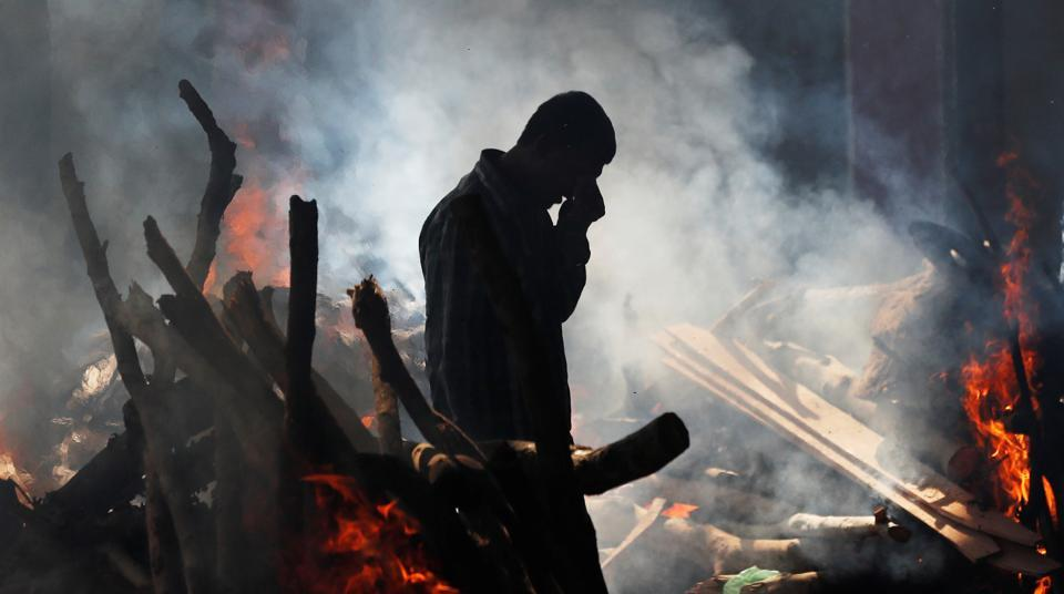 A man cries as he stands next to the burning pyre of a family member who was crushed to death on the rail tracks on Friday, at a cremation ground in Amritsar, on October 20, 2018.