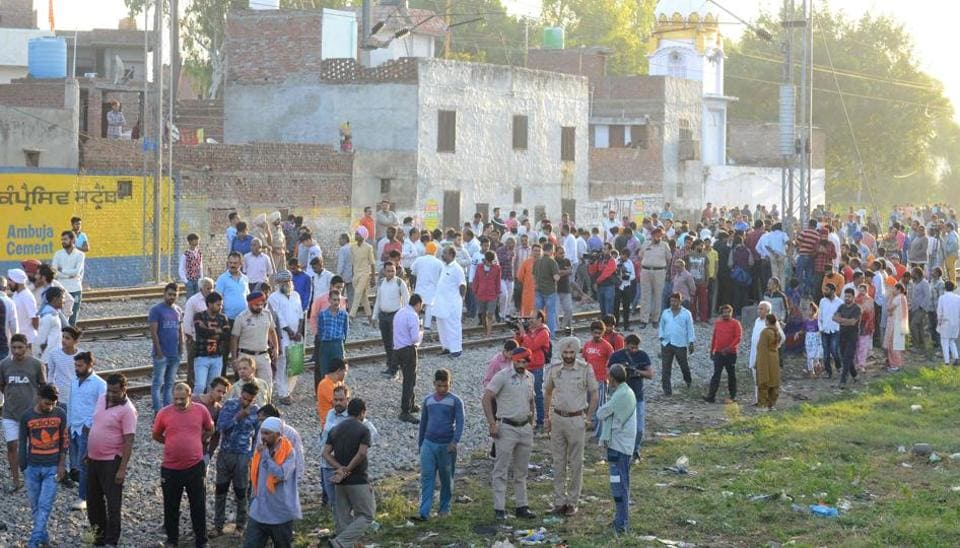 People gather near the site of a train accident at Joda Phatak in Amritsar on Saturday, a day after a train mowed down scores of people watching the Dussehra celebrations .