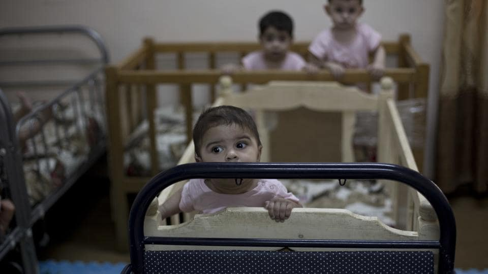 During a recent visit by The Associated Press, more than a dozen cribs were arranged end-to-end in a room set for babies. Toddlers able to stand rocked side to side, holding the sides of the cribs. There were plenty of cuddles by staff, who left no baby to cry. (Maya Alleruzzo / AP)