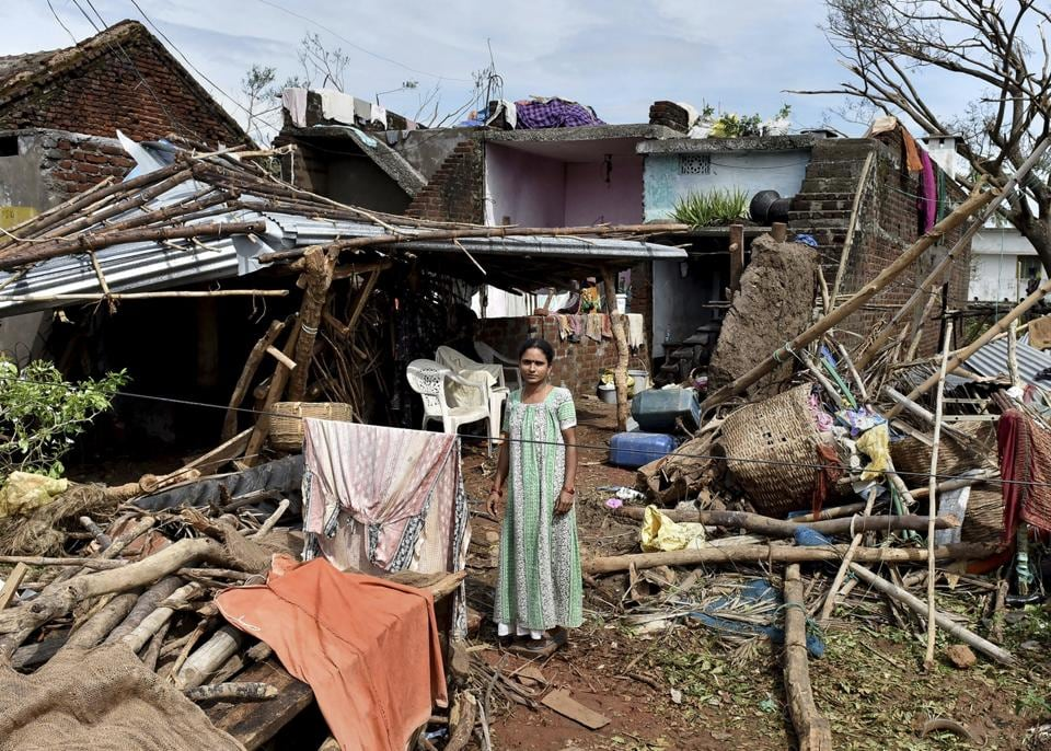 A woman stands near her damaged house hit by cyclone 'Titli'.