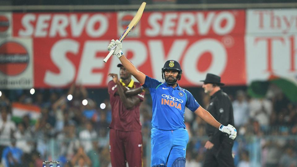 Indian batsman Rohit Sharma raises his bat after completing his century. (AFP)