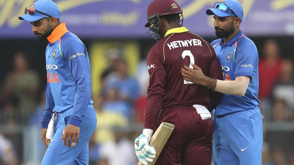 India's Mohammed Shami, right, pats West Indies' batsman Shimron Hetmyer, center, as Hetmyer leaves the field after his dismissal. (AP)