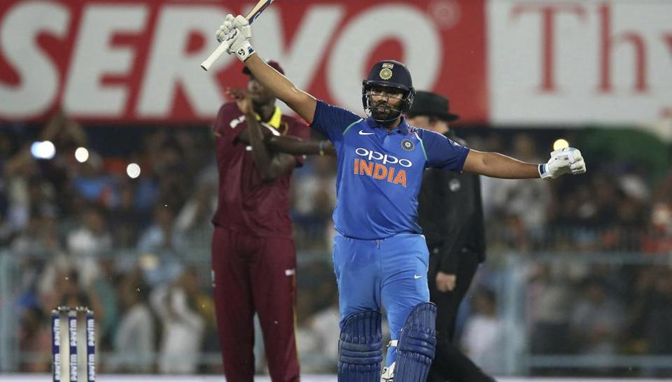 India's Rohit Sharma raises his bat to celebrate scoring a century during the first one-day international cricket match between India and West Indies in Gauhati, India, Sunday, Oct. 21, 2018.