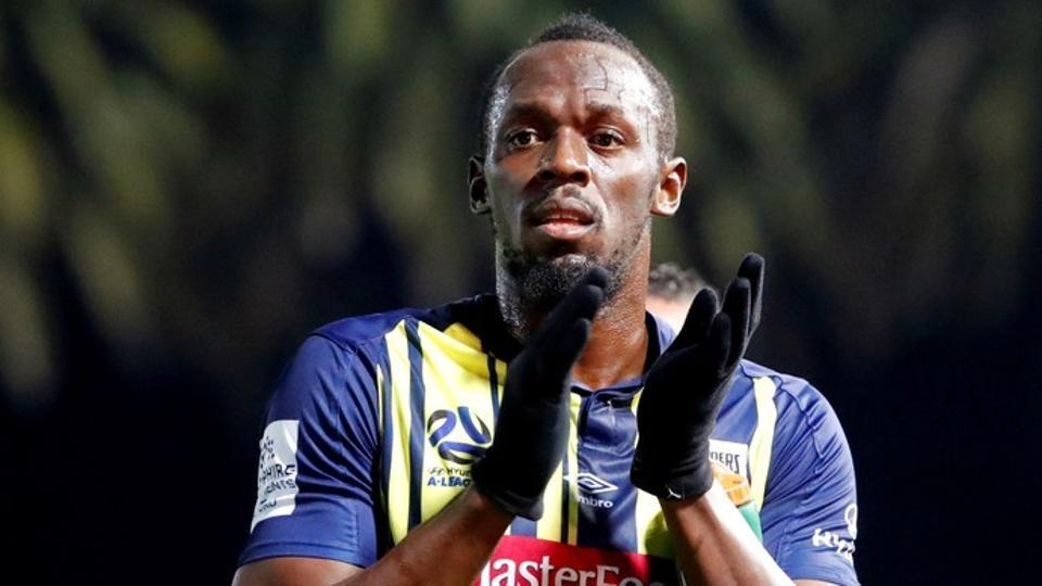 Usain Bolt applauds the fans after the match.