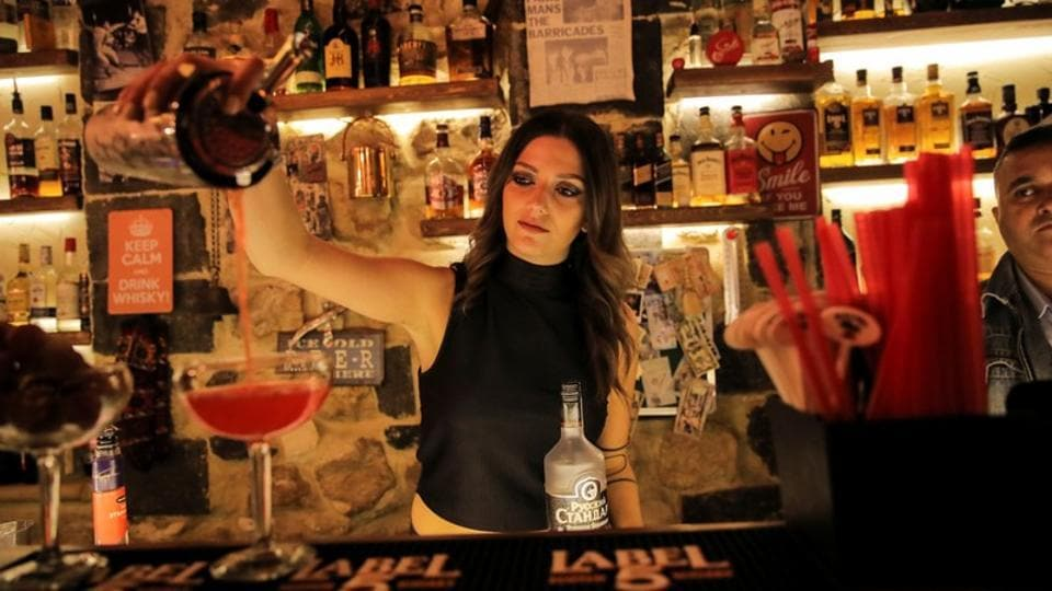 "Dana, 24, a bartender, pours a drink inside a bar in the Old City of Damascus. ""During the war, when bombs were falling, it could be days without customers, but we never stopped working,"" she said, mixing a blue moon cocktail in a shaker. (Marko Djurica / REUTERS)"