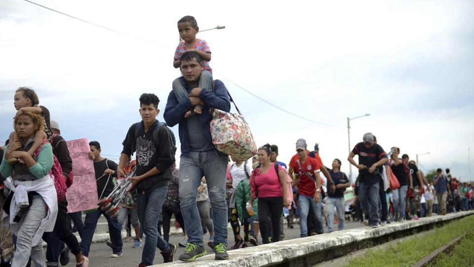 Honduran migrants rush across the border towards Mexico, in Tecun Uman, Guatemala. Thousands of Central American migrants continue an arduous trek toward the US border with many bristling at suggestions there could be terrorists among them and saying the caravan is being used for political ends by US President Donald Trump. (Oliver de Roos / AP)
