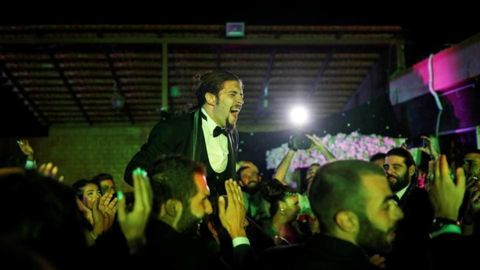 This was the first summer since 2011 without the sound of fighting in Damascus. At a wedding outside the city, the noise came rather from student rock band Kibreet - a drummer, two guitarists and a singer. The groom was carried on the shoulders of his friends and family, as people clapped around him. He swung his bride in his arms, her white dress billowing out behind. (Marko Djurica / REUTERS)