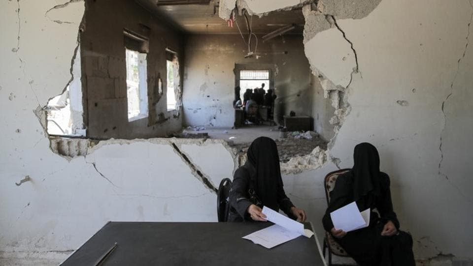 Women wait to be examined in a hospital in Douma. At one of the area's biggest hospitals, where huge shell holes are blown into the walls, medics are still operating out of the basement. The fighting in Douma only ended a few months ago, but any significant reconstruction might be very distant. (Marko Djurica / REUTERS)