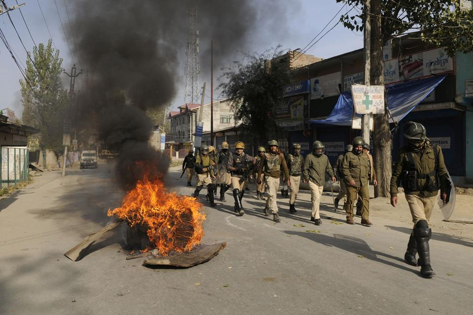 Police personnel on patrol as they pass burning tyres put up as road blockade by protesters near an encounter site in Nowgam area, Srinagar. Two militants were killed on Wednesday in a gunfight with security forces, police said. A combing operation was underway when clashes erupted with youth in the area targeting security forces, pelting stones at them. (Waseem Andrabi / HT Photo)