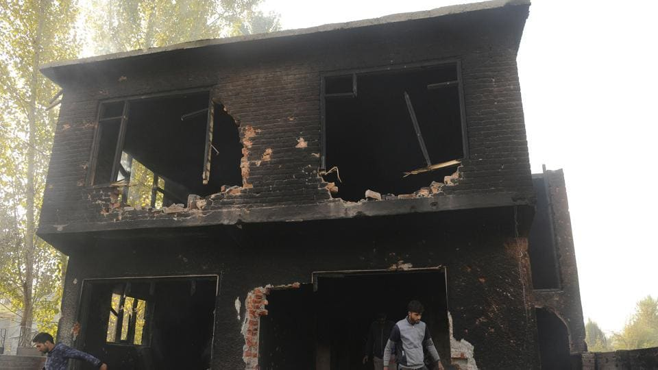People examine a house that was damaged during a gunfight between militants and security forces in the Nowgam area on the outskirts of Srinagar on October 24.