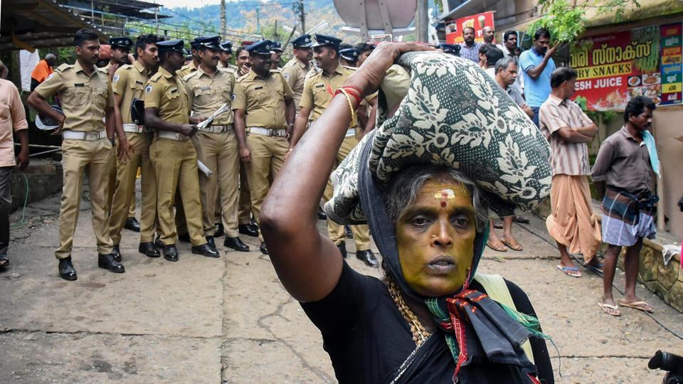 An elderly woman on her way to Sabarimala Temple as police personnel stand on guard