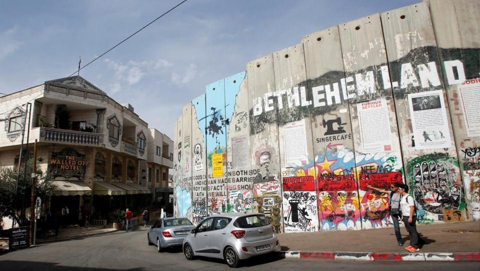 British street artist Banksy's Walled Off Hotel (L) opposite a section of the Israeli barrier in Bethlehem, occupied West Bank. The hotel is situated a few metres from Israel's separation barrier and Banksy has described the guesthouse as having the worst view of any hotel in the world, with windows overlooking the controversial wall that separates the West Bank from Israel. (Mussa Qawasma / REUTERS)