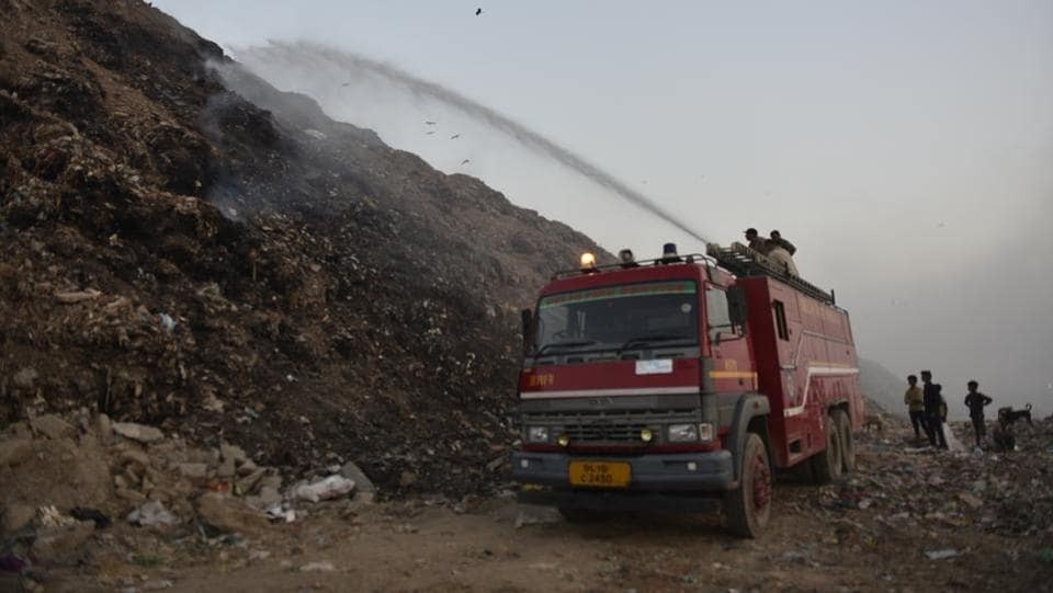 Firefighters douse a fire at Bhalswa landfill which aggravated the city's pollution, on October 23, 2018. The Supreme Court-appointed body Environment Pollution (Prevention and Control) Authority (EPCA) warned on Thursday that air pollution in the capital is likely to peak from November 1 as toxic fumes from stubble-burning in Punjab and Haryana could gush in because of a change in wind direction. (Sanchit Khanna / HT Photo)