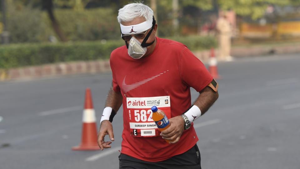 A runner wears a mask during the Airtel Delhi Half Marathon at Rajpath in New Delhi. On Thursday, Delhi also witnessed its coldest day of the season so far, when the minimum temperature dropped to 15 degrees Celsius, two degrees below normal. (Burhaan Kinu / HT Photo)