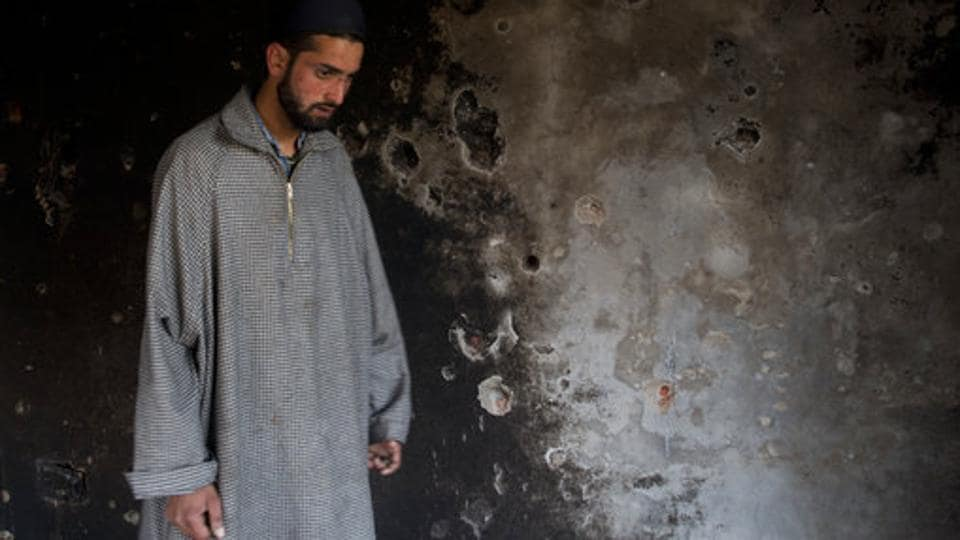 A Kashmiri man inspects a damaged house after a gunbattle between suspected militants and Indian security forces in Srinagar, Jammu and Kashmir. (Dar Yasin / AP)